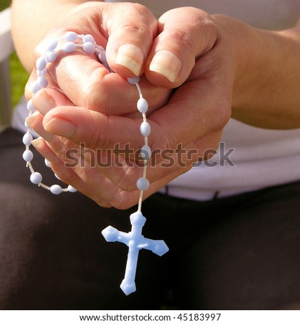 hands with rosary showing devotion and prayer - stock photo