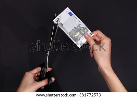 Hands with scissors cutting Euro banknote, on black background - stock photo