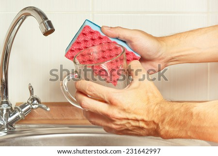 Hands with sponge and dirty cup over the sink in the kitchen - stock photo