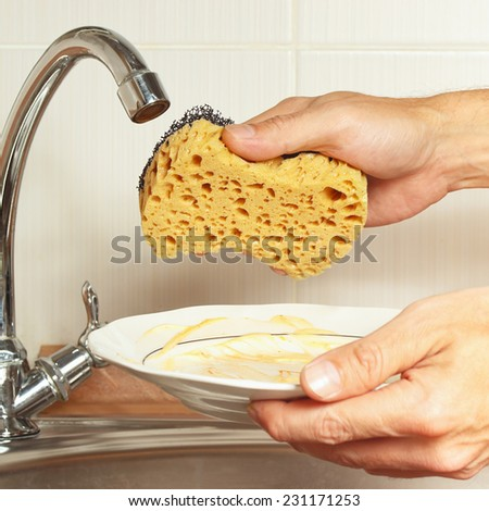 Hands with sponge and dirty dishes over the sink in the kitchen - stock photo