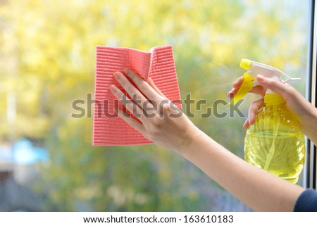 Hands with spray cleaning the window - stock photo