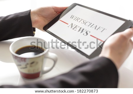 Hands with tablet and coffee reading economy news  - stock photo