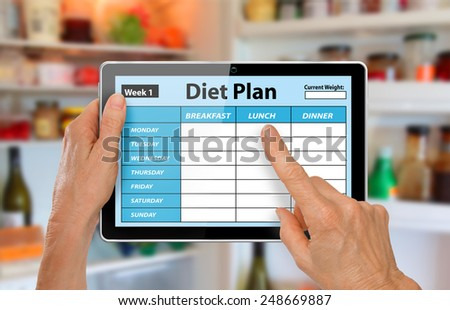 Hands with Tablet Using Diet Plan App in front of open fridge or refrigerator - stock photo