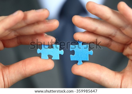Hands with two puzzles - stock photo