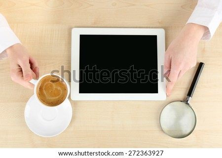 Hands working in the office with laptop, on wooden table - stock photo