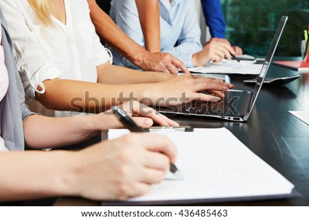 Hands working on tablet and laptop computer in the office - stock photo