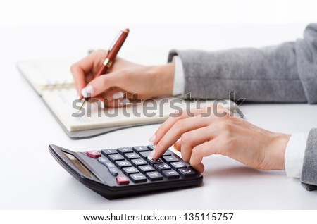 Hands working on the calculator - stock photo