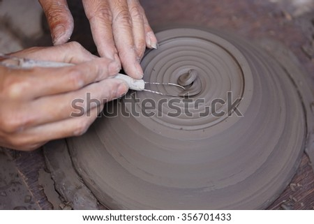 Hands working with clay on pottery wheel - stock photo