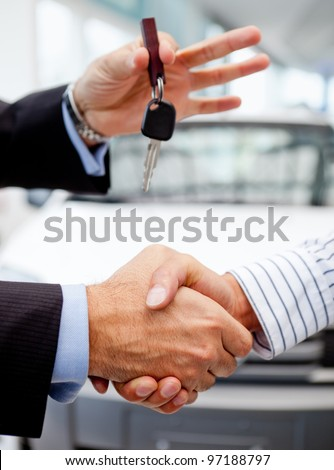 Handshake after buying a car and handling keys - stock photo