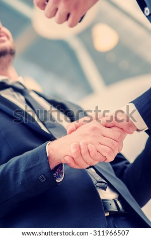 Handshake agreement. Two successful businessman standing in the restaurant and drink coffee while shaking hands with each other close-up view of hands - stock photo