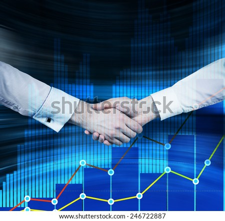 handshake at meeting on color charts background - stock photo