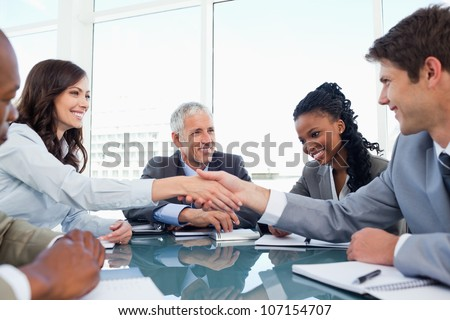 Handshake between a businesswoman and a co-worker when a meeting is ending - stock photo