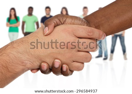 Handshake between races a over white background with unfocused people of background - stock photo
