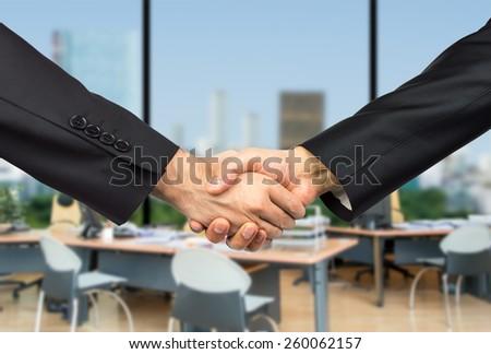 handshake business partners striking deal - stock photo