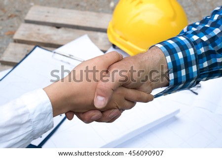 Handshake deal at construction site - stock photo