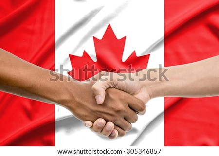 Handshake - Hand holding on Canada flag background - stock photo