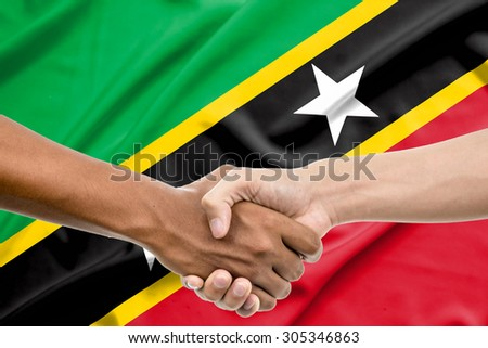 Handshake - Hand holding on Saint Kitts and Nevis flag backgroun - stock photo