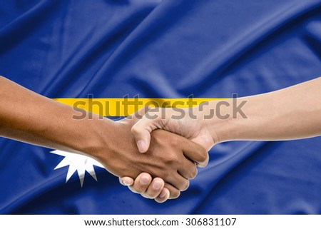 Handshake - Hand holding on tnauru flag background - stock photo