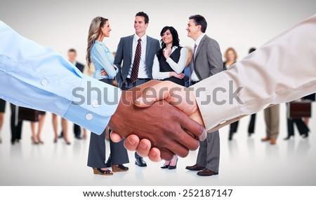 Handshake. Hands of businessman over team background. - stock photo