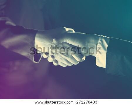 Handshake Handshaking dark and light - stock photo