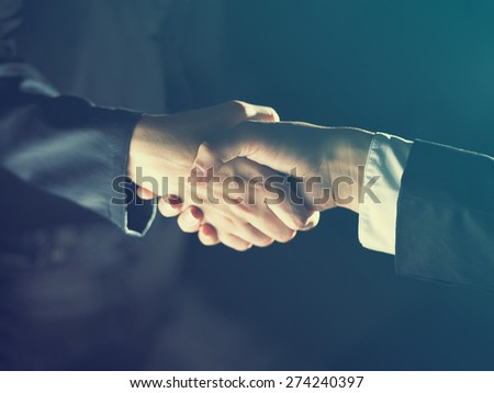 Handshake Handshaking dark and light - stock photo