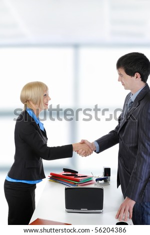 handshake happy business partners in a bright office - stock photo
