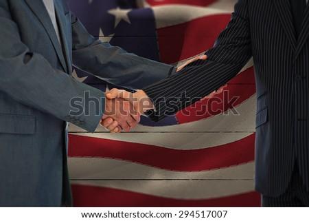 Handshake in agreement against white wood - stock photo