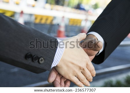 Handshake in front of the construction site - stock photo