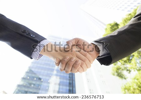 Handshake in front of the office building - stock photo