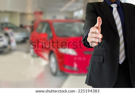 handshake of a businessman in an auto rental and sale of cars - stock photo