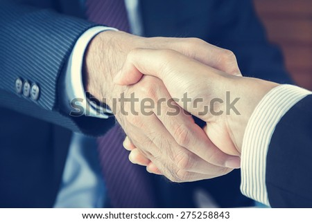 Handshake of businessmen in vintage tone - greeting , dealing, merger and acquisition concepts - stock photo
