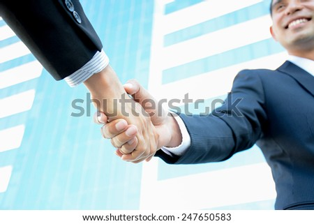 Handshake of businessmen with smiling face - greeting, dealing, partnership, merger & acquisition concepts - stock photo