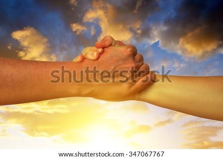 Handshake of friendship in the background sunset sky - stock photo