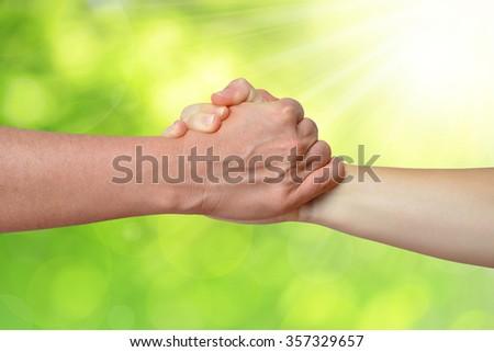 Handshake of friendship on green natural background - stock photo