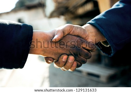handshake of two workers at a factory close up - stock photo