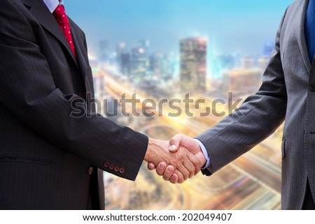 handshake on background of buildings - stock photo