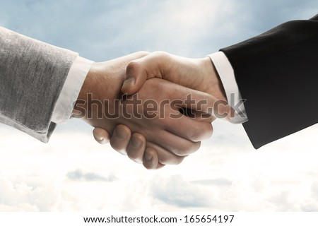 Handshake on sky background - stock photo