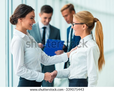 Handshake two business women on the background of their colleagues in the office - stock photo