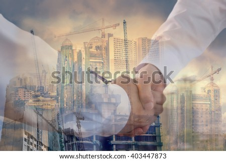 handshake two businessmen with construction sites background - stock photo
