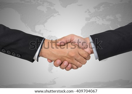 Handshake with map of the world in background, Elements of this image furnished by NASA - stock photo