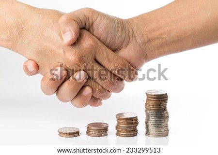handshaking gesture on top of pile of coins in graph shape - stock photo