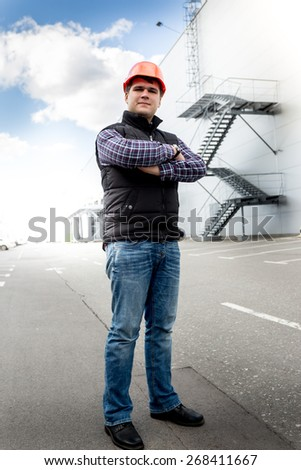 Handsome adult worker posing on road against big factory - stock photo