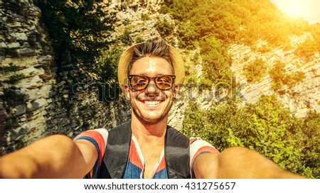 Handsome adventurous man taking selfie at mountain. Caucasian young man smiling at the camera. - stock photo