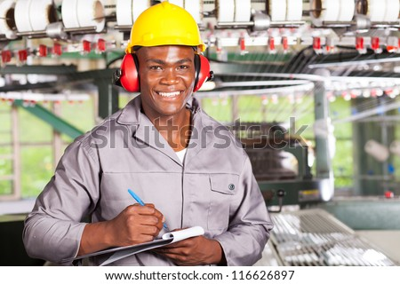 handsome african american blue collar worker portrait inside factory - stock photo