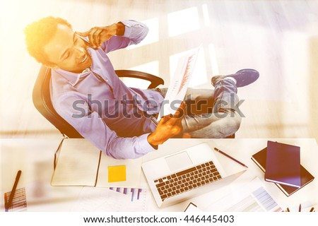 Handsome african american businessman with business report in hand talking on phone at office desk with laptop and various other items. View from above. Toned image - stock photo