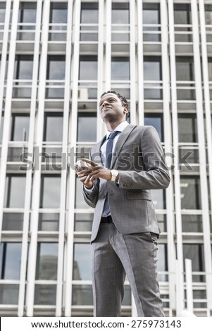 Handsome african american businessman with smart phone looking up. Behind building with windows - stock photo