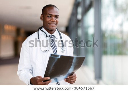 handsome african american male doctor holding x ray - stock photo