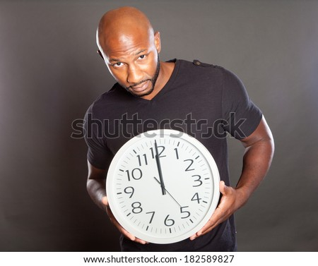 Handsome african american man holding a clock that reads 12:00 midnight or noon looking at the camera with concern - stock photo