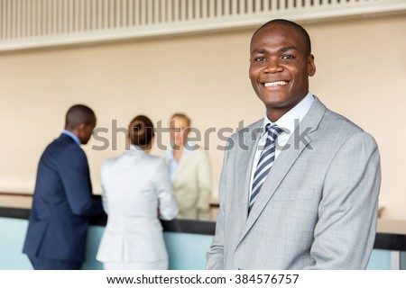 handsome african american manager standing at hotel reception - stock photo