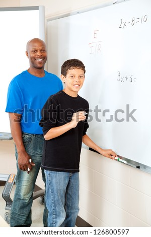 Handsome african-american teacher helps student at the board with math. - stock photo